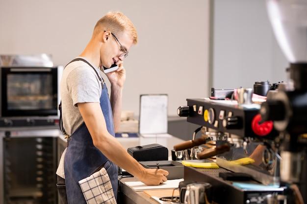 Молодой официант или работник кафетерия записывает заказы клиентов в блокноте, разговаривая с ними по мобильному телефону на рабочем месте