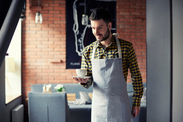 一杯のコーヒーを提供する若いウェイター
