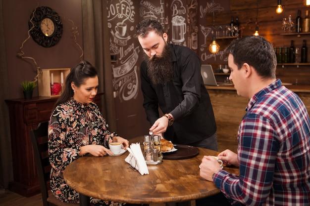 カフェのテーブルで男性と女性の顧客に食事を提供する若いウェイター。流行に敏感なパブ。