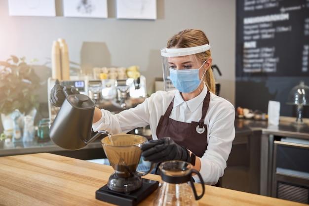 커피를 양조하는 다른 방법을 보여주는 젊은 웨이터