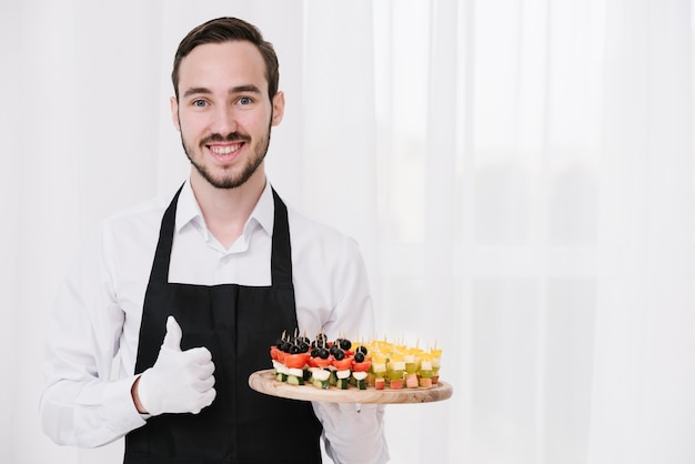 Young waiter showing appetizers