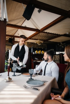 A young waiter in a stylish apron demonstrates and offers a fine wine to a beautiful couple in a restaurant. customer service.