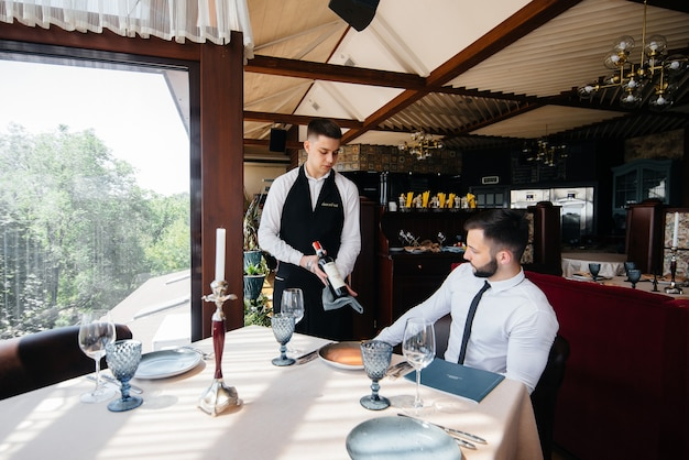 A young waiter in a stylish apron demonstrates and offers a fine wine to a client in a restaurant. customer service.
