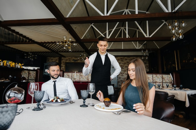 A young waiter in a stylish apron serves a table with a beautiful couple in a refined restaurant. customer service.