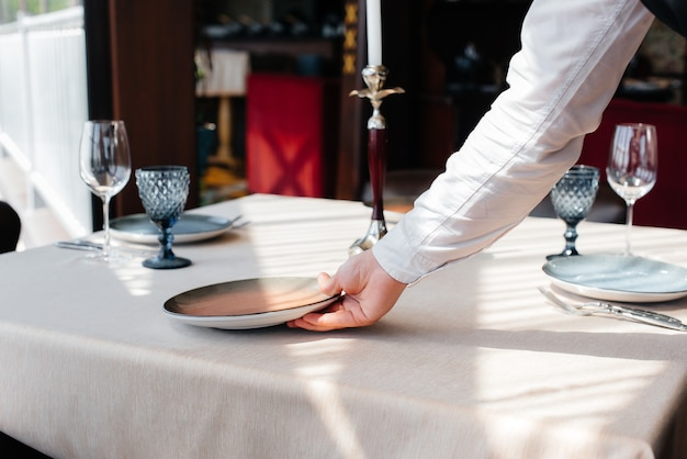 A young waiter in a stylish uniform is engaged in serving the table in a beautiful gourmet restaurant close-up. restaurant activity, of the highest level.