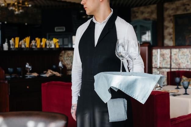 A young waiter in a stylish uniform stands with glasses on a tray near the table in a beautiful gourmet restaurant close-up. restaurant activity, of the highest level.