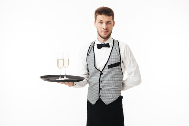 Young waiter in uniform holding tray with glasses of champagne while thoughtfully