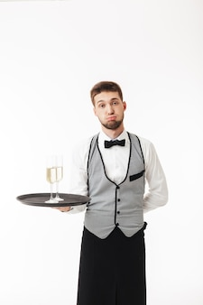 Young waiter in uniform holding tray with glasses of champagne while tiredly
