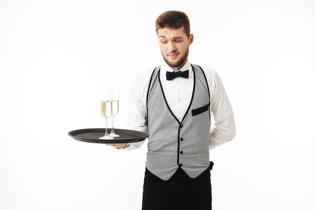 Young waiter in uniform thoughtfully