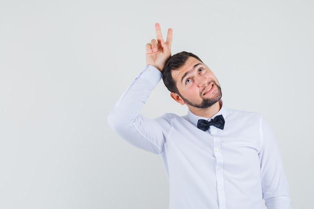 Giovane cameriere in camicia bianca che tiene v-segno dietro la testa come le corna e sembra divertente, vista frontale.