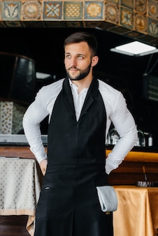 A young waiter with a beard puts on an apron and prepares for a working day in a fine restaurant.