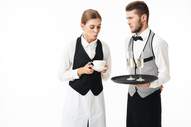 Young waitress blowing on cup of coffee while serious waiter holding tray with glasses of champagne thoughtfully