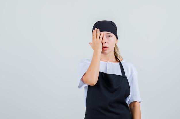 Giovane cameriera che copre gli occhi con la mano in uniforme e grembiule