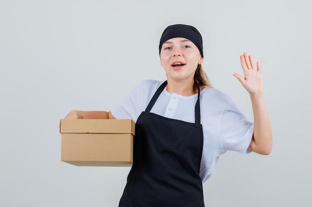 Giovane cameriera tenendo la scatola di cartone e mostrando la palma in uniforme e grembiule