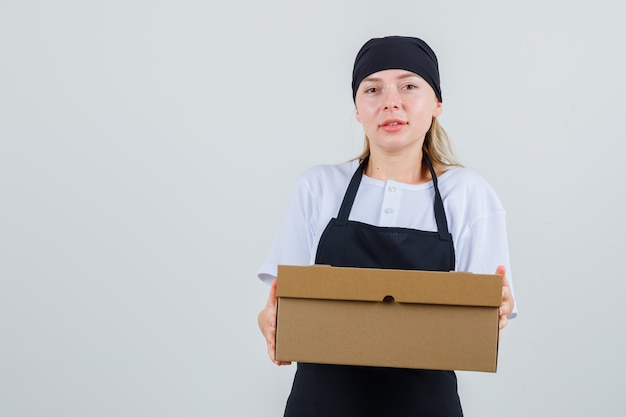 Young waitress holding cardboard box in uniform and apron