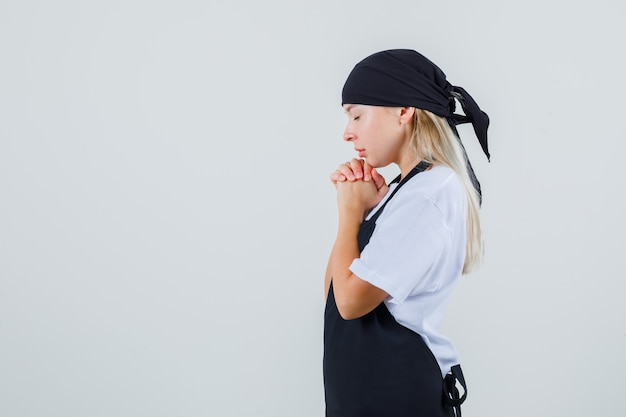 Young waitress holding clasped hands in praying gesture in uniform and apron and looking peaceful .