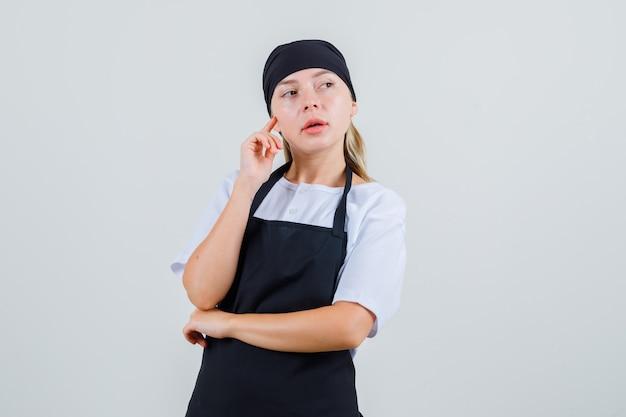 Giovane cameriera tenendo il dito sulla guancia in uniforme e grembiule e guardando pensieroso