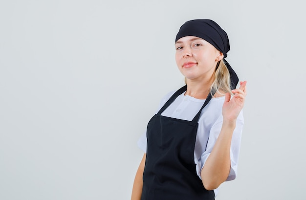 Young waitress holding fingers crossed in uniform and apron and looking merry