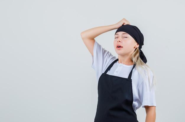 Giovane cameriera che tiene il pugno sulla testa in uniforme e grembiule e sembra dispiaciuto
