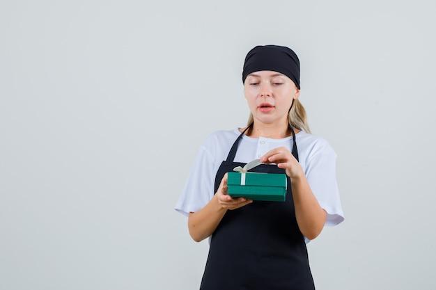 Giovane cameriera che tiene il contenitore di regalo in uniforme e grembiule e sembra curioso