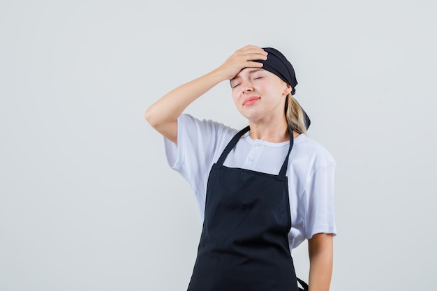 Giovane cameriera che tiene la mano sulla fronte in uniforme e grembiule e sembra smemorato