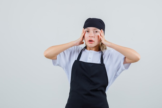 Giovane cameriera che si tiene per mano a testa in uniforme e grembiule e sembra esausta