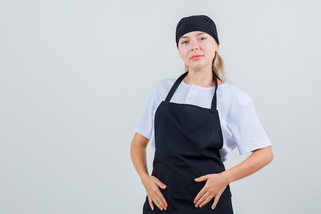 Giovane cameriera che tiene le mani sul suo grembiule in uniforme e sembra ottimista