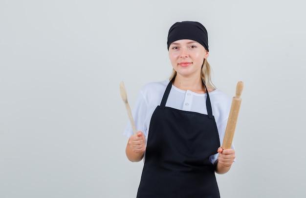 Giovane cameriera che tiene cucchiaio di legno e mattarello in uniforme e grembiule e sembra allegro
