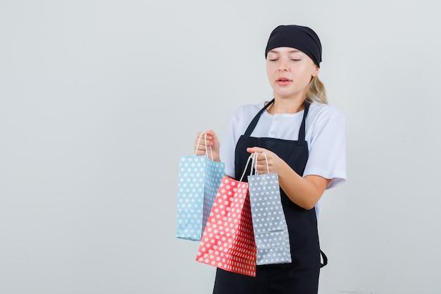 Молодая официантка в униформе и фартуке держит бумажные пакеты