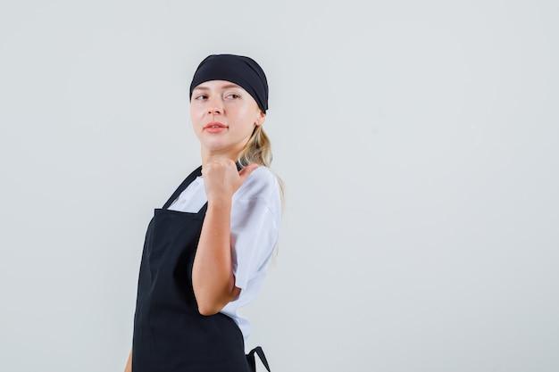 Молодая официантка в униформе и фартуке указывает большим пальцем назад и выглядит уверенно