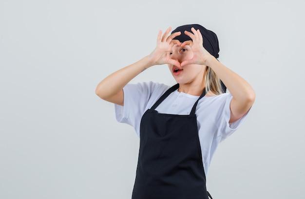 Молодая официантка в униформе и фартуке, показывая жест сердца на глаз