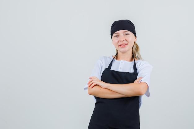 Молодая официантка в униформе и фартуке стоит со скрещенными руками и радостно