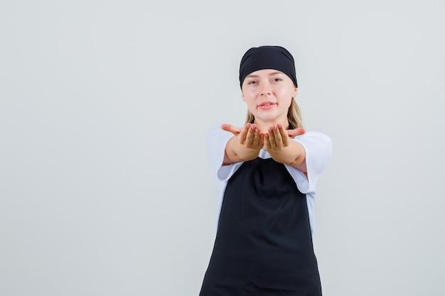 Giovane cameriera che invita a venire in uniforme e grembiule e sembra allegra