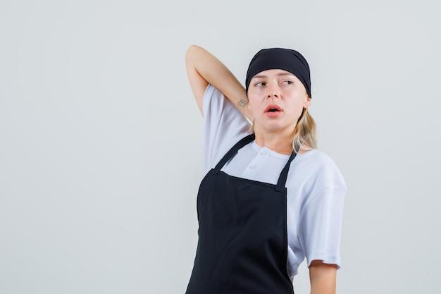 Giovane cameriera che osserva da parte con la mano sul collo in uniforme e grembiule