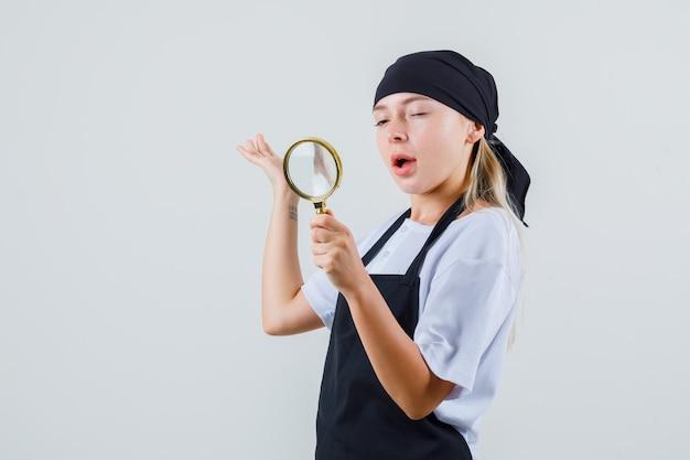 制服とエプロンで拡大鏡とまばたきの目を見て若いウェイトレス
