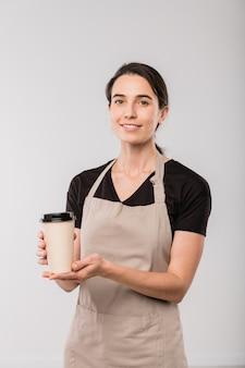 孤立してカメラの前に立っている間あなたにホットコーヒーのグラスを与えるエプロンのカフェの若いウェイトレス