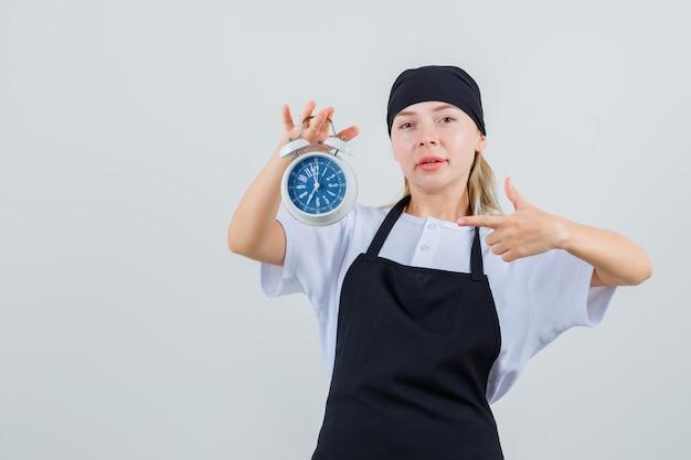 Молодая официантка, указывая на будильник в униформе и фартуке