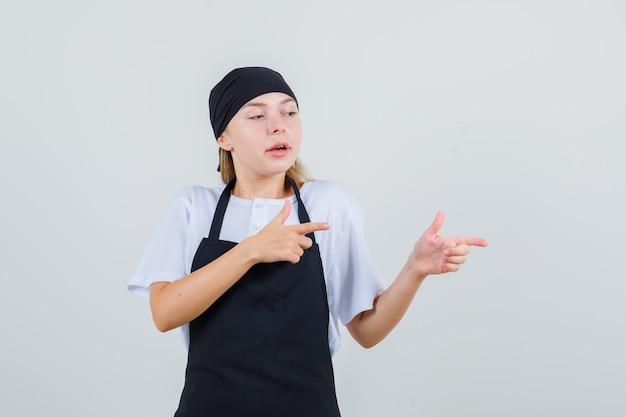 Молодая официантка указывает в сторону, показывая жест пистолета в форме и фартуке