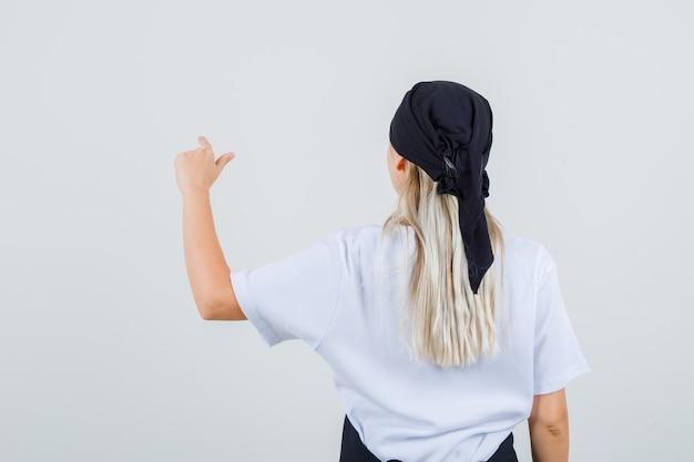 Giovane cameriera che punta a qualcosa in uniforme e grembiule vista posteriore.