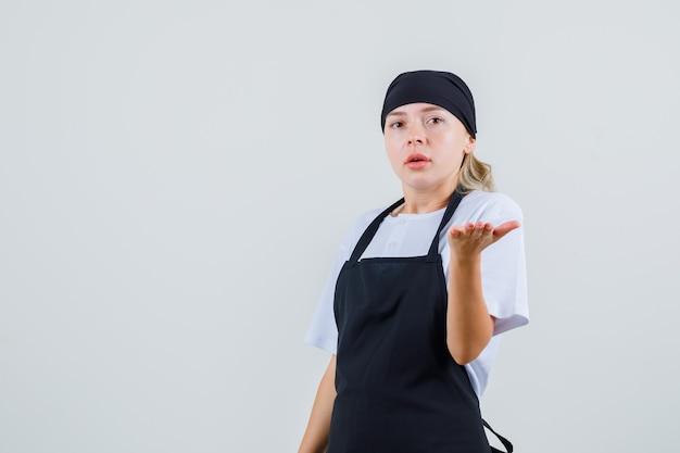 Giovane cameriera che alza il palmo in modo interrogativo in uniforme e grembiule