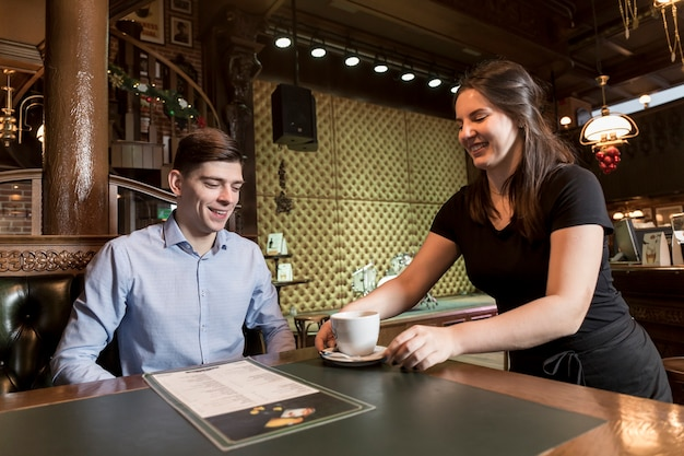Young waitress serving coffee to customer