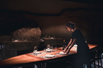 Young waitress setting table