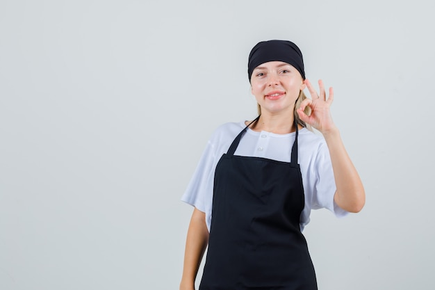 Young waitress showing ok gesture in uniform and apron and looking cheerful