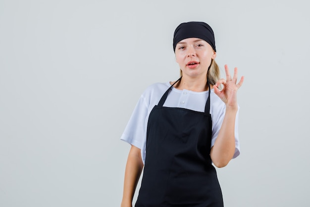 Young waitress showing ok gesture in uniform and apron and looking confident