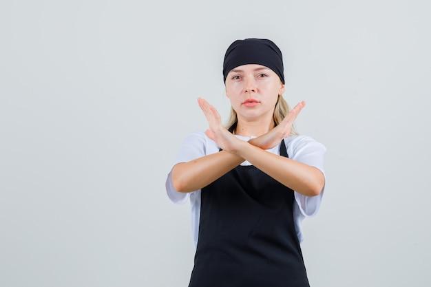 Giovane cameriera che mostra il gesto di arresto in uniforme e grembiule e sembra seria