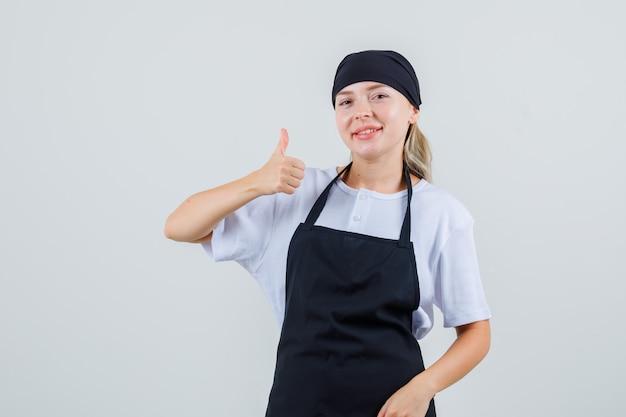 Giovane cameriera che mostra pollice in su in uniforme e grembiule e sembra allegra