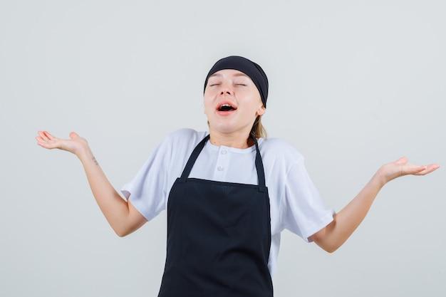 Giovane cameriera che allarga le palme da parte in uniforme e grembiule e sembra grata