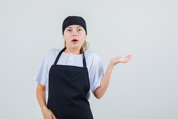 Young waitress spreading raised palm aside in uniform and apron and looking puzzled