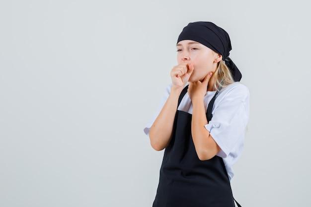 Giovane cameriera che soffre di tosse in uniforme e grembiule e sembra malata