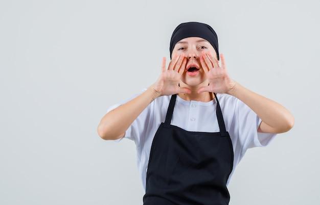 Молодая официантка рассказывает секрет в форме и фартуке